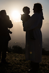 20 April 2019, Jerusalem: Photographer Ben Gray (left) at work, as Rev. Jeni Falkman Grangaard and her two-and-a-half-year-old son Amos share a moment after an Easter Sunday sunrise service at Jabal Allah (God's Mountain) on the Mount of Olives in Jerusalem, held by the Lutheran Church of the Redeemer (English-speaking congregation).