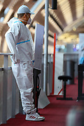 """An Asian air passenger is seen wearing a white hazmat suit, as well as surgical face protective masks to curb the spread of Coronavirus pandemic outbreak, wait for his flight in Terminal E2 at the Charles de Gaulle Airport in Paris, on Saturday, Dec 12, 2020. France recorded about 2,351,372 coronavirus infections, with 57,567<br /> of them resulting in death and 175,891 of them recovered. Internal European borders will remain open but external borders are closed except for essential travel. All travellers arriving in France will be tested at airports and ports says the government website adding that the """"Masks must be worn at all times in public transport"""". (VXP Photo/ Vudi Xhymshiti)"""