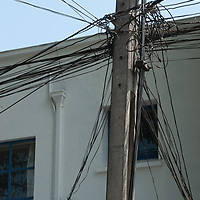 A tangle of electric and phone wires festoon a power pole in downtown Santiago,.