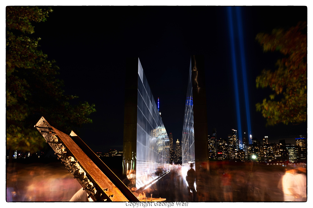 Every year on September 11th, many people gather in the evening at the Empty Sky Memorial in Liberty State Park. The crowd is sombre and quiet, conversations are hushed. In the foreground, metal from the twin towers. In the background, the symbolic twin blue lights stretch up to the sky. And the ghostly reflection of a passerby on the names of loved ones lost shine on.