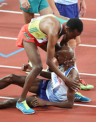 London, August 12 2017 . Muktar Edris, Ethiopia, winner, helps Mo Farah, Great Britain, up after beating Farah to gold in the men's 5000m final on day nine of the IAAF London 2017 world Championships at the London Stadium. © Paul Davey.