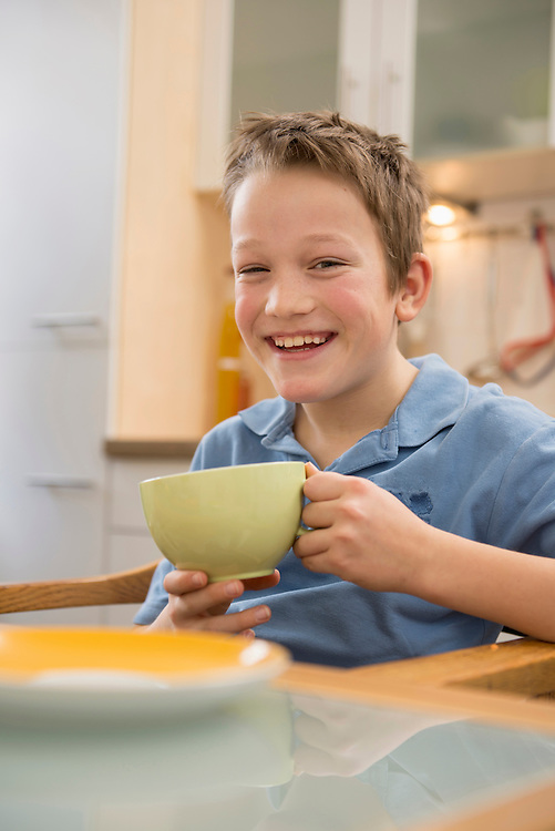 Portrait of smiling boy holding cup in kitchen