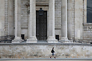 Man wearing a face mask walks past St Pauls Cathedral, which is eerily quiet and silent aside from a  few pedestrians on empty streets as lockdown continues and people observe the stay at home message in the capital on 11th May 2020 in London, England, United Kingdom. Coronavirus or Covid-19 is a new respiratory illness that has not previously been seen in humans. While much or Europe has been placed into lockdown, the UK government has now announced a slight relaxation of the stringent rules as part of their long term strategy, and in particular social distancing.