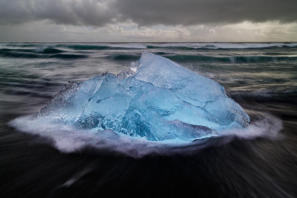 Intimate landscape of icebergs and rushing waves along the iceberg beach in Jokulsarlon, Iceland.