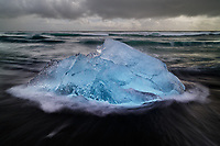Intimate landscape of icebergs and rushing waves along the iceberg beach in Jokulsarlon, Iceland.