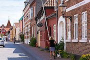 Woman walking dog in Gronnegade in medieval Ribe centre, South Jutland, Denmark