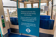 Warning signs on a very quiet DLR - The 'lockdown' continues for the Coronavirus (Covid 19) outbreak in London.