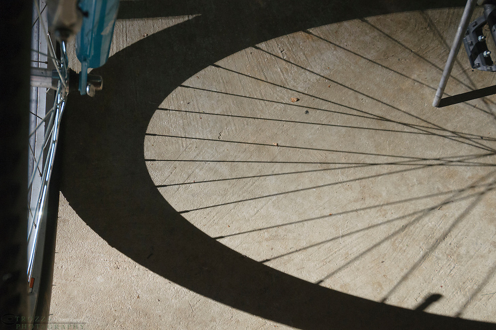 Long shadows created by strong light against a bicycle.