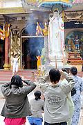 Worshippers at prayer before statue of Bodhisattva, Pho Hien Bo Tat, at Buddhist Temple on Nui Ba Den (Black Lady Mountain), Tay Ninh, Vietnam