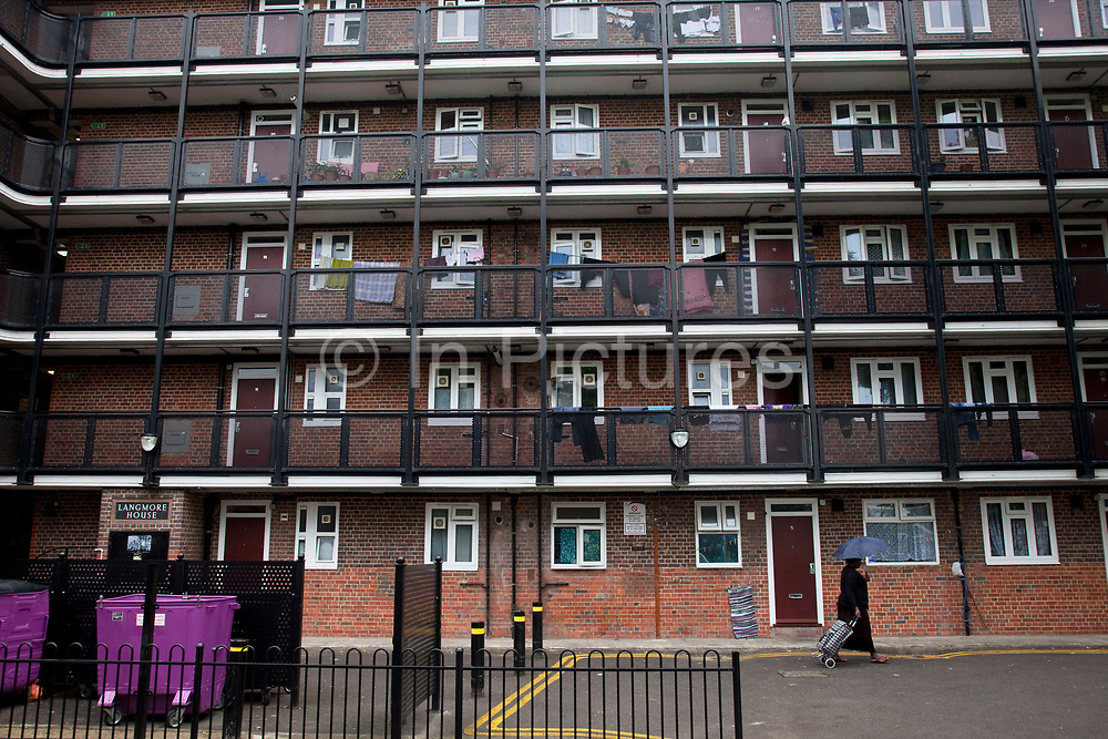 People near to council flats in Tower Hamlets, East London. Many people are at risk of losing their homes in London with the introduction of new benefit rules, which may push many people renting or who own council apartments out of the city. Tower Hamlets is a poor and over populated borough with many people living in small homes in high rise apartment blocks.