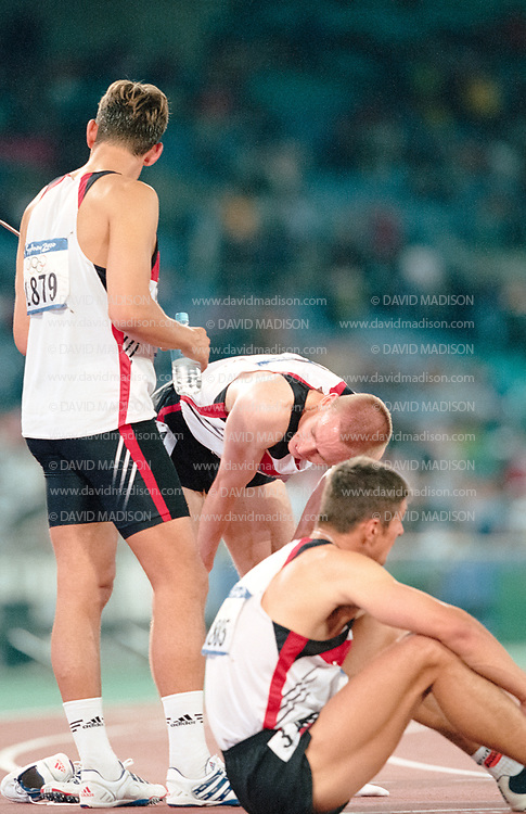 SYDNEY -  SEPTEMBER 28:  Mike Maczey #1879 of Germany, Stefan Schmid #1885 of Germany, and Frank Busemann #1863 of Germany recover after running in the Decathlon 1500 meter race of the Athletics competition of the 2000 Olympic Games held on September 28, 2000 at Stadium Australia in Sydney, Australia.  (Photo by David Madison/Getty Images)