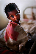 War's most innocent victim, a child clad only in a grain sack awaits treatment at a hospital in Ethiopia run by the International Committee of the Red Cross during the devastating 1983-1985 famine and civil war. Founded to protect victims of armed conflict, this neutral Swiss intermediary, based in Geneva, sees itself as the conscience of an imperfect world.  © Steve Raymer / National Geographic Creative