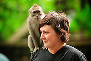 Apr. 21 - UBUD, BALI, INDONESIA: A tourist with a long tail macaque on her head in the Monkey Forest in Ubud, Bali. Hundreds of long-tailed macaques (Macaca fascicuiaris) live in the forest, which is also the site of several Hindu temples and is sacred in Bali society.  Photo by Jack Kurtz/ZUMA Press