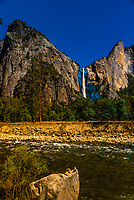 Man relaxing on a large rock next to the Merced River with Cathedral Rock and Bridalveil Fall in background, Yosemite National Park, California USA.
