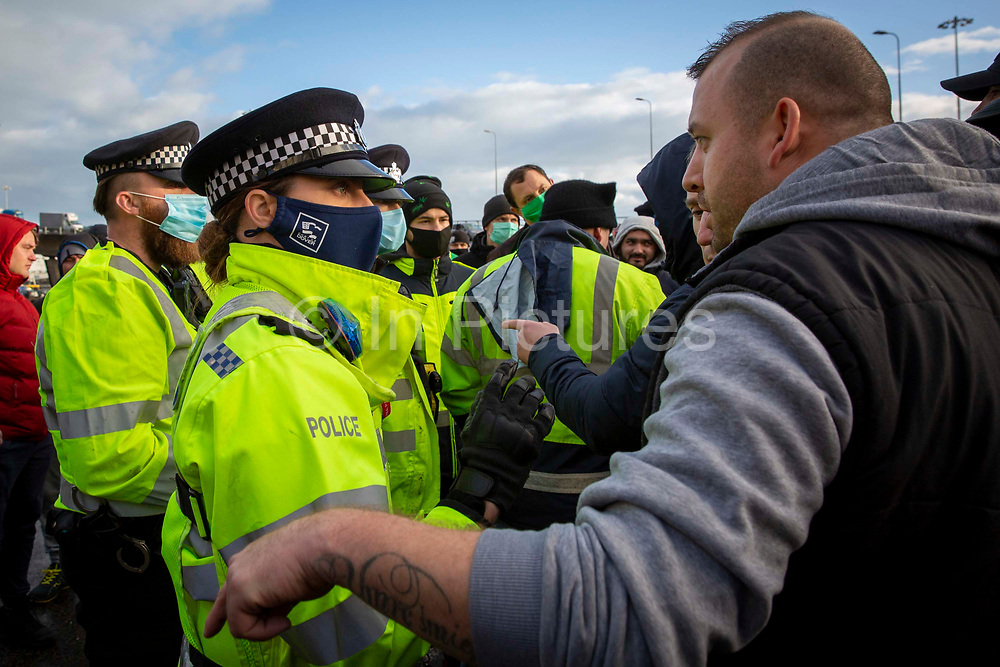 Tensions are high between police and drivers who have been waiting over 48 hours for the Port of Dover to re-open, on the 23rd of December 2020, Dover, Kent, United Kingdom. The French border was closed due to a new strain of COVID-19 all travellers are now waiting to receive a COVID-19 test before they can board a ferry to Calais, France. Dover is the nearest port to France with just 34 kilometres 21 miles between them. It is one of the busiest ports in the world. As well as freight container ships it is also the main port for P&O and DFDS Seaways ferries.