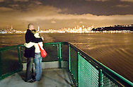 A young couple hugs and watches Seattle slip into the distance on a romantic crossing of Puget Sound, Washington, USA
