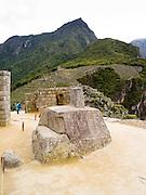 The Incan ruins of the Intihuatana, a special altar, at Machu Picchu, with Montaña Machu Picchu in the background, near Aguas Calientes, Peru.