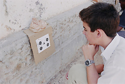 School boy examining target during shooting lesson,
