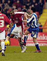 Photo: Leigh Quinnell.<br /> Bristol City v Huddersfield Town. Coca Cola League 1. 10/02/2007. Bristol Citys Kevin Betsy fights his way past Huddersfields Matthew Young.