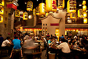 Chinese restaurant interior in Zhung Guan Cun area in Beijing, China. At lunchtime this restaurant is alive with activity of both customers and waiting staff. Lanters are suspended above emblazoned with the names of various dishes available here.