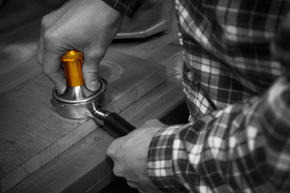 Kyle Von Hoetzendorff tamps some coffee to make an espresso in the Chris King kitchen.