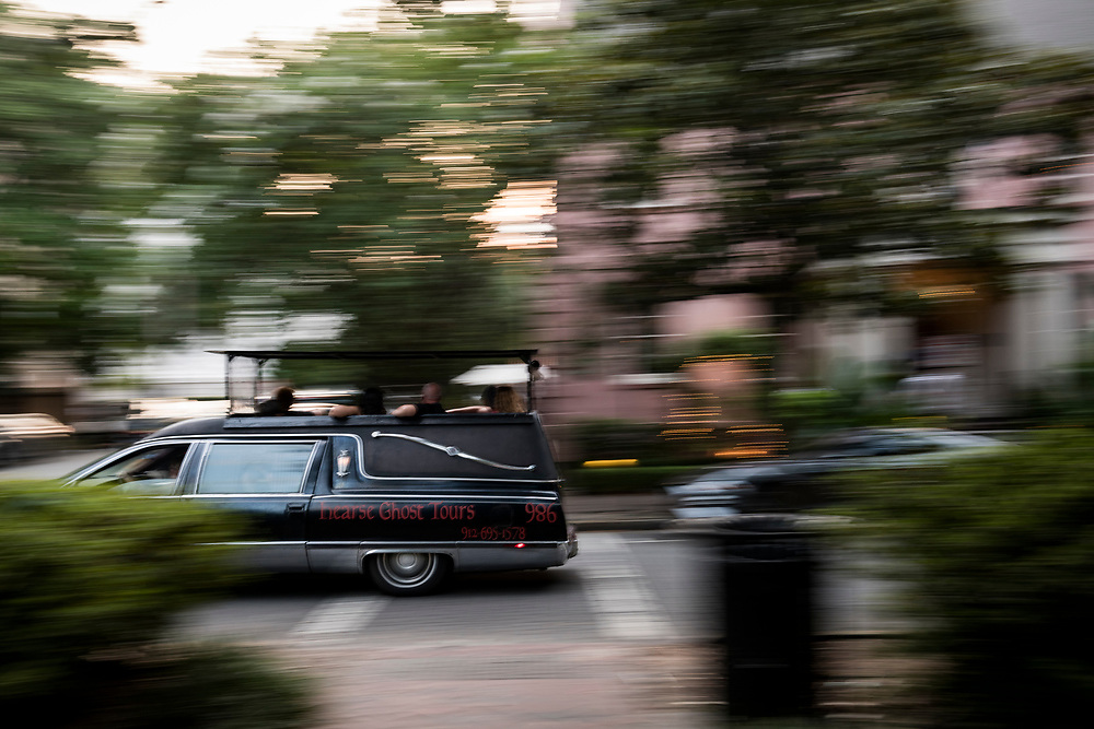 Savannah, Georgia - July 30, 2021: A hearse ghost tour drives past a square at sunset in downtown Savannah.