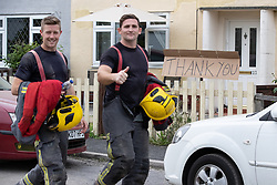 © Licensed to London News Pictures. 03/08/2019. Whaley Bridge, UK. Firefighters walk past home made placards , put out by residents , thanking emergency services for protecting their town . The town of Whaley Bridge in Derbyshire remains evacuated after heavy rain caused damage to a slipway on the Toddbrook Reservoir , threatening homes and businesses with flooding. Photo credit: Joel Goodman/LNP