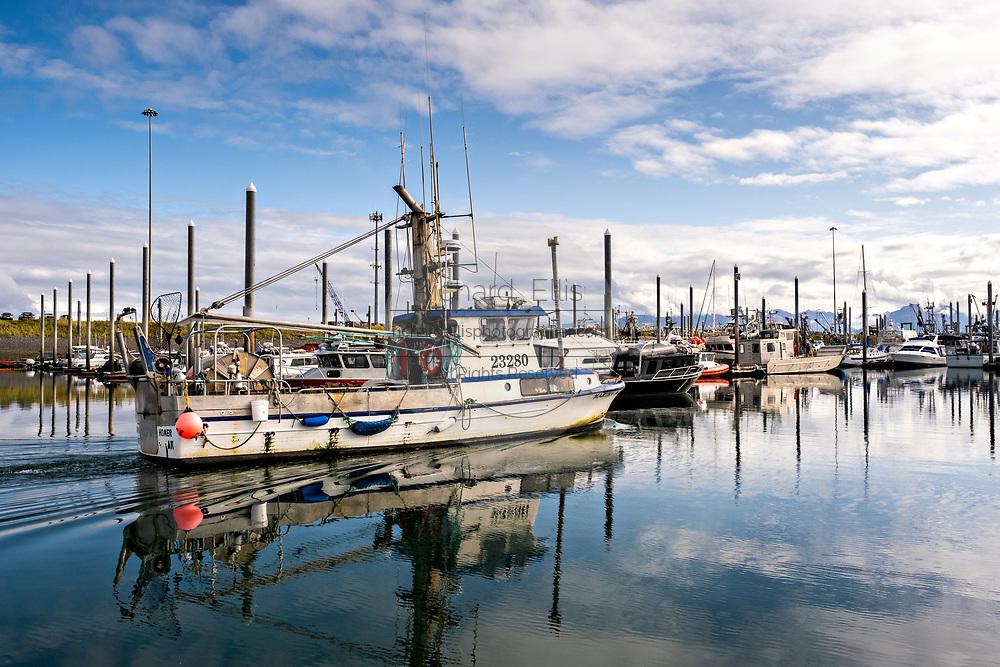 A commercial fishing boat motors through the City of Homer Port & Harbor marina on the Kachemak Bay overlooking the Kenai Mountains in Homer, Alaska.