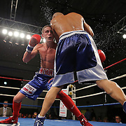"""Anthony Mercado (left) fights Javier Perez during a """"Boxeo Telemundo""""  boxing match at the Kissimmee Civic Center on Friday, July 18, 2014 in Kissimmee, Florida.  (AP Photo/Alex Menendez)"""