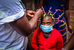May 9, 2020: Martha Apisa, a 12 year waits during the final touches of her Corona Virus braiding style to e done by her close neighbour sisters hair dressers, Sharon Oyiella 23 years and her fellow Diana Andai. (Credit Image: © Donwilson Odhiambo/ZUMA Wire)