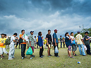 "24 JULY 2014 - BANGKOK, THAILAND: People line up for free food at the happiness party on Sanam Luang. The Thai Junta is organizing a series of public events throughout Thailand meant to bolster public opinion. The events are called ""restoring happiness to the people"" parties. They feature historic pageants, music, food, health checks and free haircuts. The party in Bangkok is on Sanam Luang, the Royal Parade Ground, which is near the Grand Palace and the Ministry of Defense.    PHOTO BY JACK KURTZ"