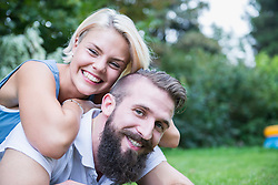 Portrait of a happy young couple lying in garden, Bavaria, Germany
