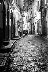 A deserted cobblestone street in Procida Italy. It is amazing the peace and tranquility you can find in an ancient Italian Village at 5AM in the morning. <br /> <br /> I was walking to the other side of the Island to take a sunrise photo but had to stop several times for street shots. <br /> <br /> A day or two later I ruined my luggage doing this same walk, me tiny wheels only made it half way across the island.