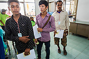 09 JULY 2014 - ARANYAPRATHET, SA KAEO, THAILAND: Cambodian migrant workers line up for photos and ID cards in the Thai Immigration One Stop Service Center in Aranyaprathet on the Thai-Cambodian border. More than 200,000 Cambodian migrant workers, most undocumented, fled Thailand in early June fearing a crackdown by Thai authorities after a coup unseated the elected government. Employers have been unable to fill the vacancies created by the Cambodian exodus and the Thai government has allowed them to return. The Cambodian workers have to have a job and their employers have to vouch for them. The Thai government is issuing temporary ID cards to allow them to travel openly to their jobs. About 800 Cambodian workers came back to Thailand through the Aranyaprathet border crossing Wednesday. The Thai government has opening similar service centers at three other crossing points on the Thai-Cambodian border.    PHOTO BY JACK KURTZ