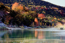 Stock photo of the changing fall foliage along a river in the Texas Hill Country