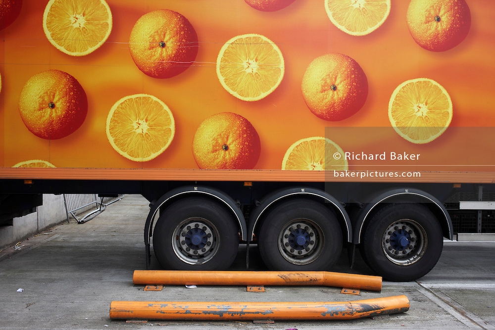 A long-distance lorry is parked at the Sainsbury's 700,000 sq ft (57,500sq m) supermarket warehouse and distribution depot at Waltham Point London England. With round wheels echoing the circles of oranges, long-distance vehicles depart every two minutes, 24 hours a day, 364 days a year to 80 UK stores and handling 2.5m supermarket cases a week. Transporting refrigerated perishable foodstuffs, these lorries are ever-present on the nation's motorways and A roads, plying back and forth to re-supply the supermarkets. Food orders are conveyed with sorter systems that group products together, ordering them to favour the layout of specific stores, optimising how the shelves are stacked..