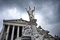 Photo of statue in front of Parliament building in Vienna, Austria with a cloudy sky.