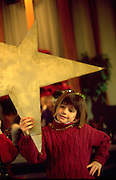 Child age 8 holding the Holy star during Christmas pageant.  WesternSprings  Illinois USA