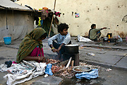 Homeless women and their children cook by the side of the road at a temporary shelter in Karol Bagh, New Delhi, India