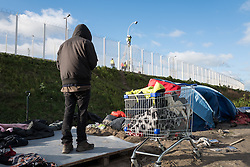 © London News Pictures. Calais, France. 15/01/16. An Eritrean man gathers his posessions in a shopping trolley as a security camera is installed above the fence at the Calais 'Jungle' refugee camp. French authorities are to bulldoze a 100-metre 'buffer zone' between the camp and the adjacent motorway, which leads to the ferry port. Photo credit: Rob Pinney/LNP