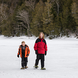 Two boys snowshoe on Henderson Lake on the Tahawus Tract, Newcomb, New York. Adirondack Mountains. One source of the Hudson River.