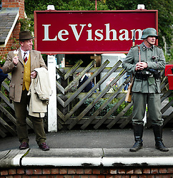 © Licensed to London News Pictures. <br /> 15/10/2016. <br /> Levisham, UK.  <br /> <br /> A men dressed in period clothing looks at a German Army re-enactor as he eats an ice cream at Levisham station during the North Yorkshire Moors Railway Wartime Weekend event. <br /> The annual event brings together re-enactors and enthusiasts along the length of the NYMR heritage steam railway line to recreate the feel of the war years of the 1940's. <br /> <br /> Photo credit: Ian Forsyth/LNP