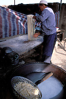 China. Sinkiang Province (Xinjiang).  Kashgar (Kashi). Old city bazar. Ouigour population. Sunday market. Noodle maker. // Chine. Province du Sinkiang (Xinjiang). Kashgar (Kashi). Bazar de la vieille ville. Population Ouigour. Marché du dimanche. Fabrication des nouilles.