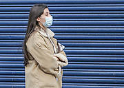 12th, March, 2021. Cheltenham, England. A member of the public walks through the town centre wearing a mask.