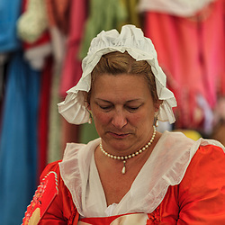 Colonial woman wearing a white house cap and orange dress at a British America reenactment camp.