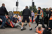 An angry motorist moves an Insulate Britain climate activist blocking a slip road from the M25 at Junction 25 as part of a campaign intended to push the UK government to make significant legislative change to start lowering emissions on 15th September 2021 in Enfield, United Kingdom. The activists, who wrote to Prime Minister Boris Johnson on 13th August, are demanding that the government immediately promises both to fully fund and ensure the insulation of all social housing in Britain by 2025 and to produce within four months a legally binding national plan to fully fund and ensure the full low-energy and low-carbon whole-house retrofit, with no externalised costs, of all homes in Britain by 2030 as part of a just transition to full decarbonisation of all parts of society and the economy.