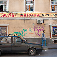 TIMISOARA, ROMANIA - APRIL 21:  A man walks in front of Banca Populara Aurora on April 21, 2013 in Timisoara, Romania.  Romania has abandoned a target deadline of 2015 to switch to the single European currency and will now submit to the European Commission a programme on progress towards the adoption of the Euro, which for the first time will not have a target date. (Photo by Marco Secchi/Getty Images)