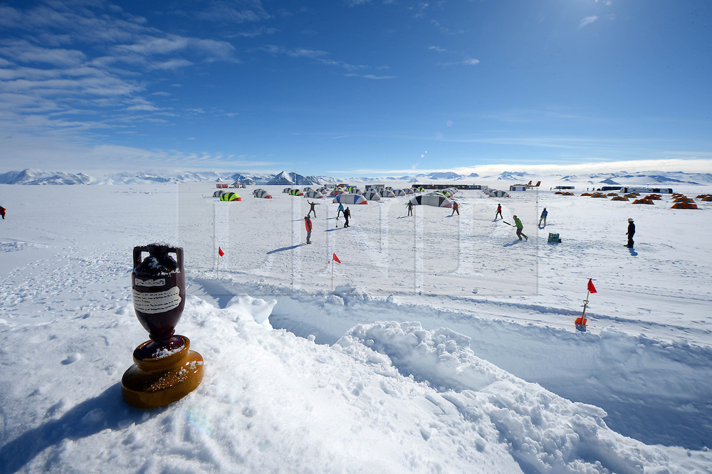 """© Licensed to London News Pictures. Union Glacier, Antarctica. An Ashes replica model is in foreground. Competitors from the Antarctic Ice Marathon play a game of impromptu """"Ashes"""" cricket at the Union Glacier camp, Antarctica ahead of the 2013 Antarctic Ice Marathon, which takes place  just a few hundred miles from the South Pole at the foot of the Ellsworth Mountains.. The majority of players were either Australian and English. It was declared a sporting draw. Photo credit: Mike King/LNP"""