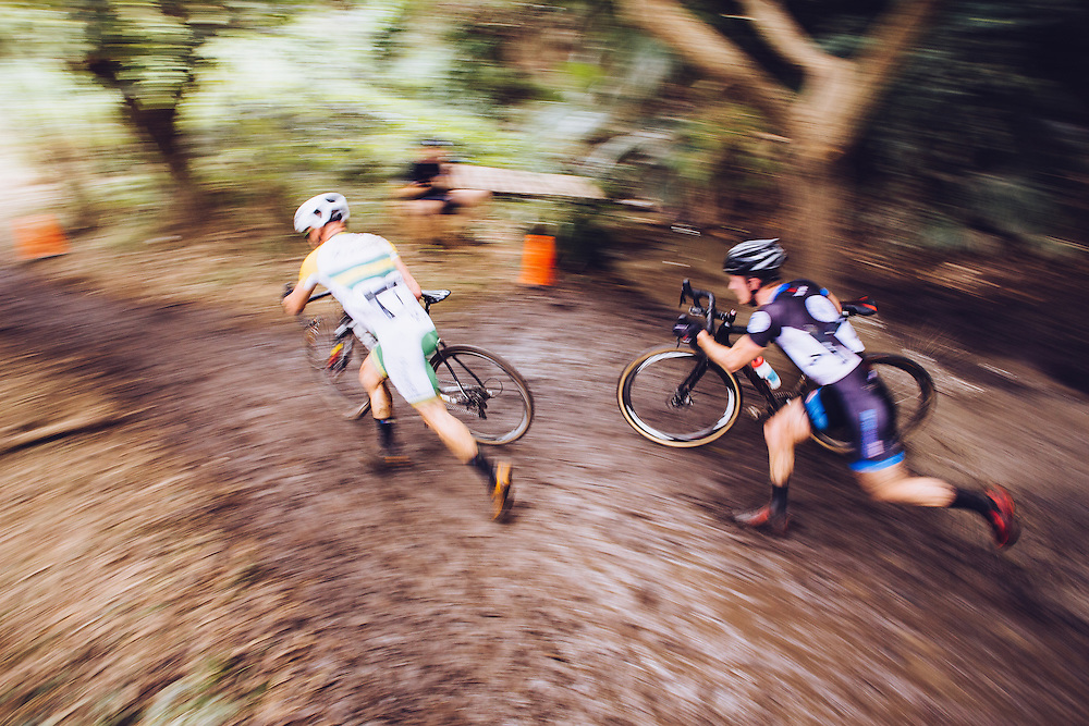 Australian elite mens cyclocross riders running their bikes through a muddy obstacle in the Brisbane leg of the national cyclocross series.
