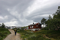 Mann med stor ryggsekk går mot Jøldalsbua i Trollheimen, man with big backpack is walking towards Jølstadbua in Trollheimen